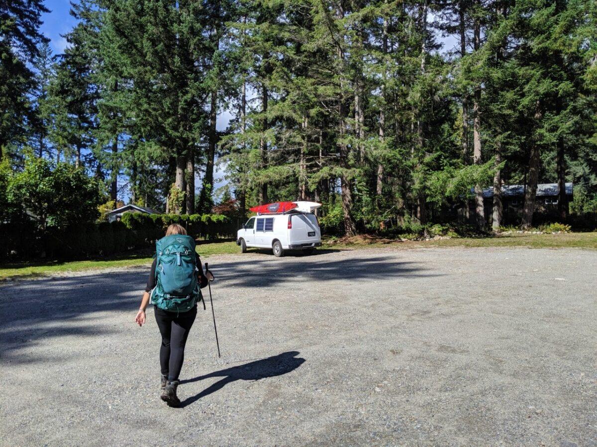 Gemma walking towards white van in Community Hall parking lot