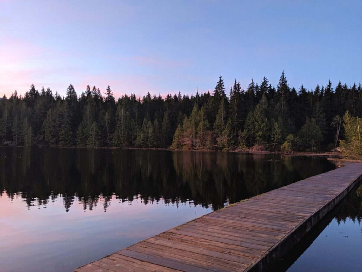 An exceptionally calm lake with tinges of pink from the sunset, with a dock