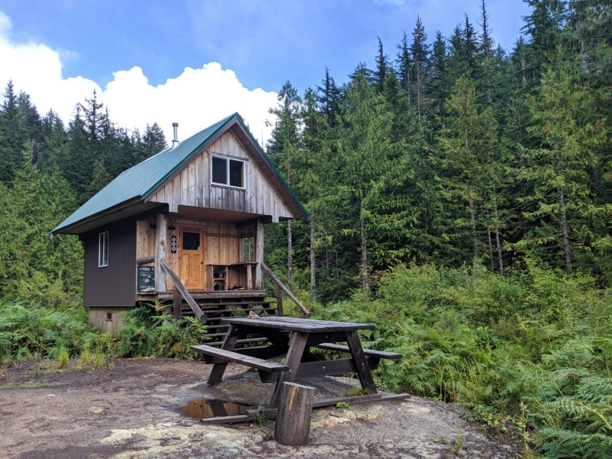 Picnic table in front of a two story backcountry hut on the Sunshine Coast Trail