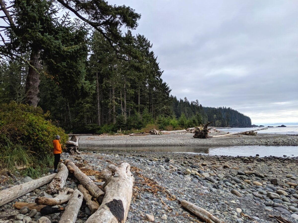 Gemma standing in orange jacket next to rocky beach on the Juan de Fuca coast