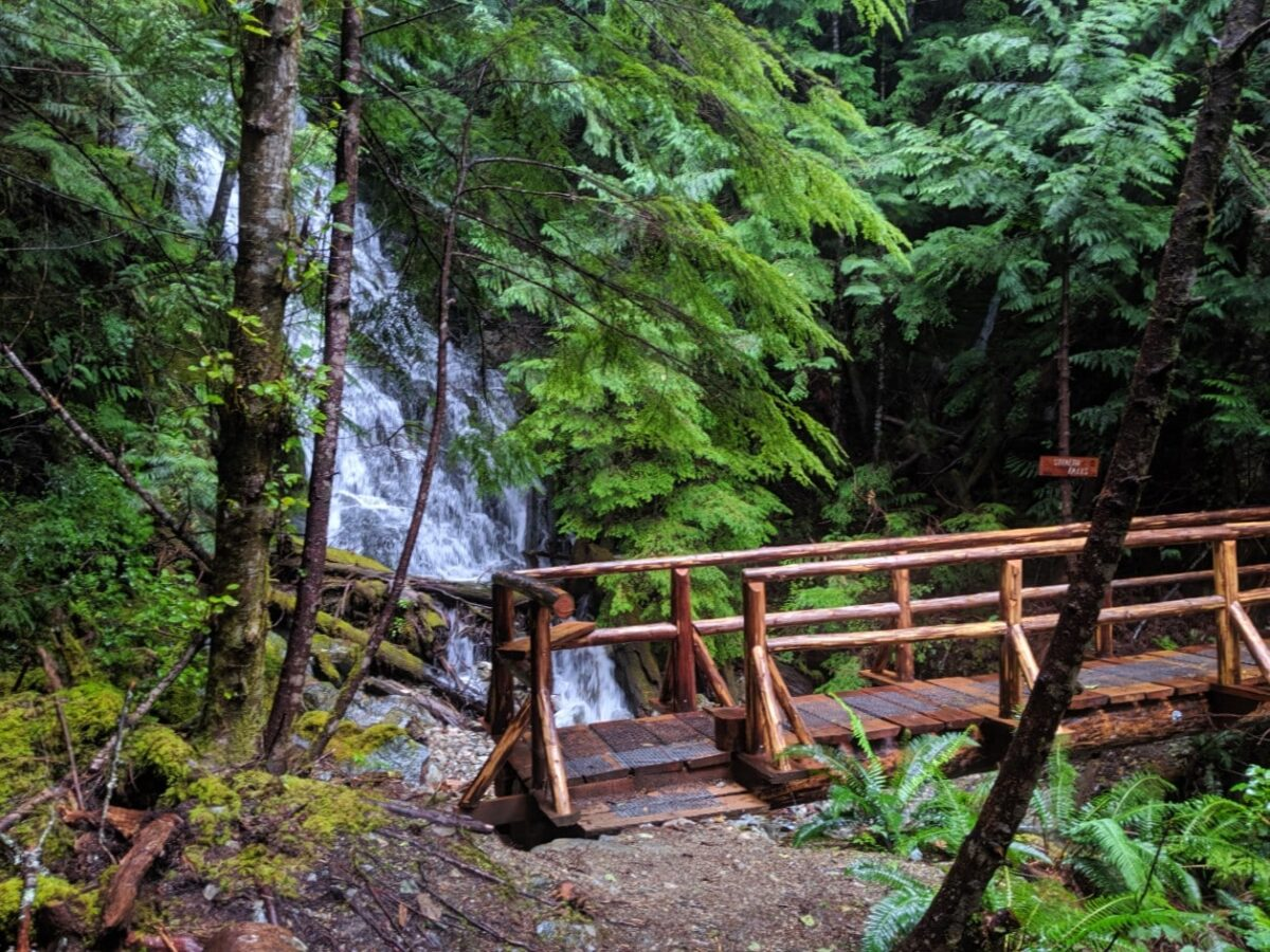 Waterfall cascading behind a wooden bridge on the Sunshine Coast Trail