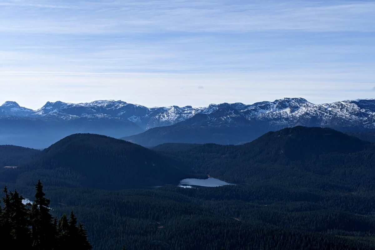 A backdrop of snow capped mountains look over alpine lakes and forest