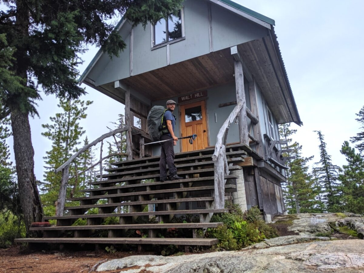 JR walking up the stairs of the two story Walt Hill backcountry hut
