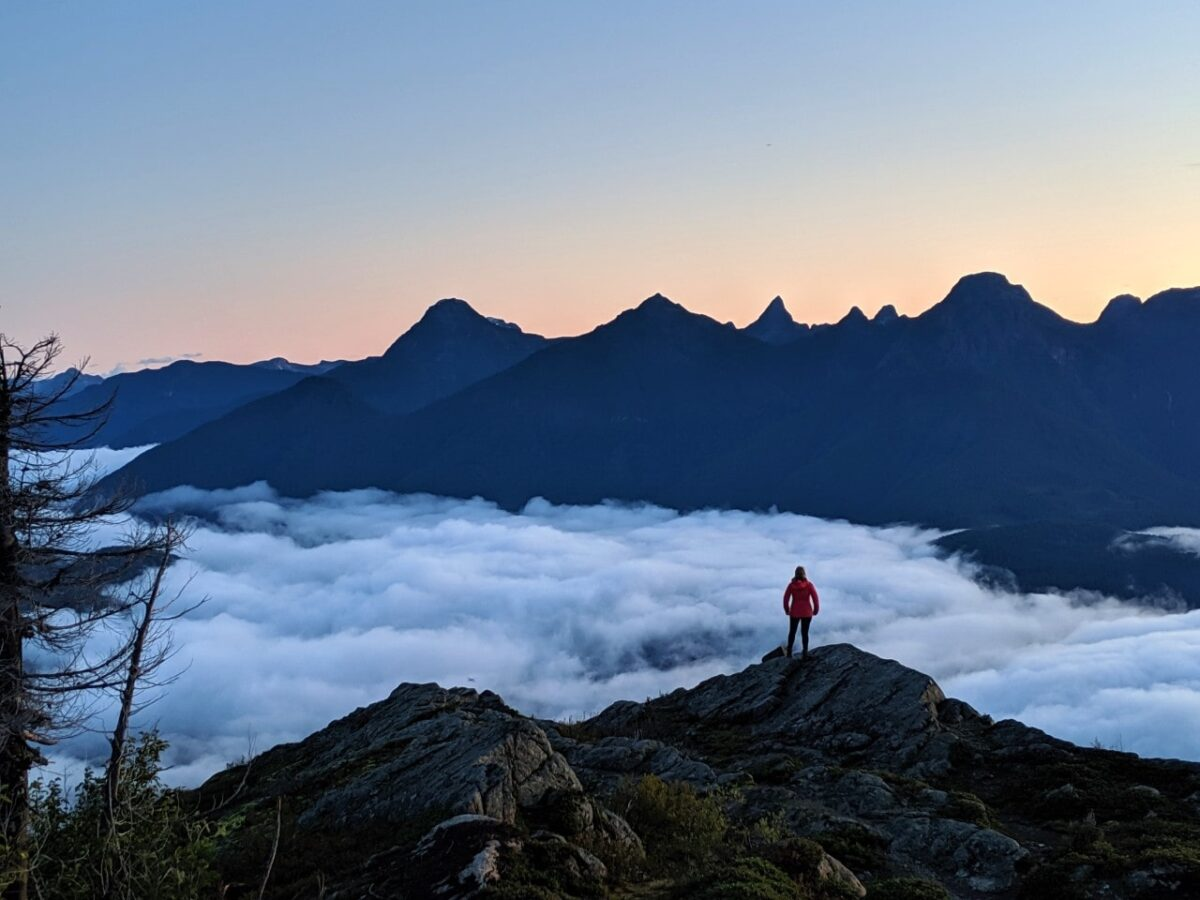 Gemma standing on top of a mountain with sun rising behind peaks, cloud blocking the land below