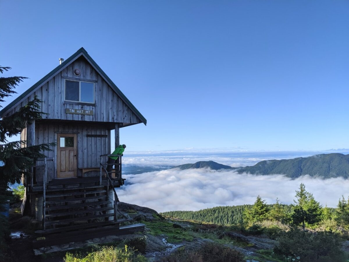 JR standing on the deck of the Tin Hat Mountain hut looking at the cloud covered views