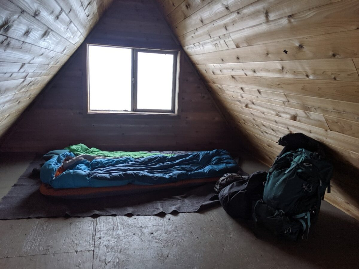 Enclosed sleeping loft of Tin Hat Mountain hut with two sleeping bags unrolled on the ground with a backpack nearby