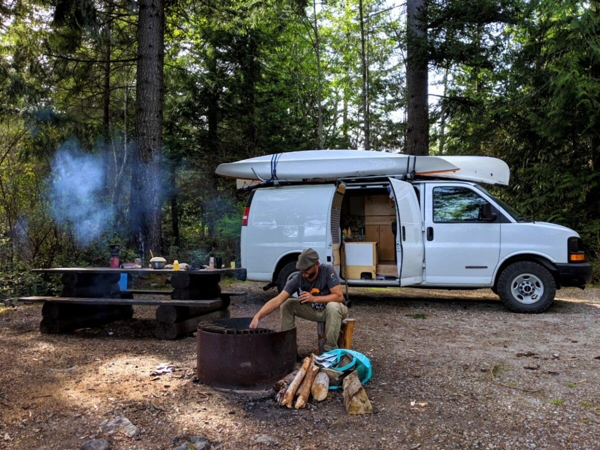 A white van (with one open door) is parked in front of a picnic table and fire pit, where JR is tending a campfire