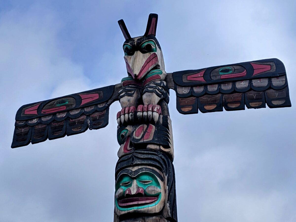 The top of a red, green, black and natural totem pole with a raven's head