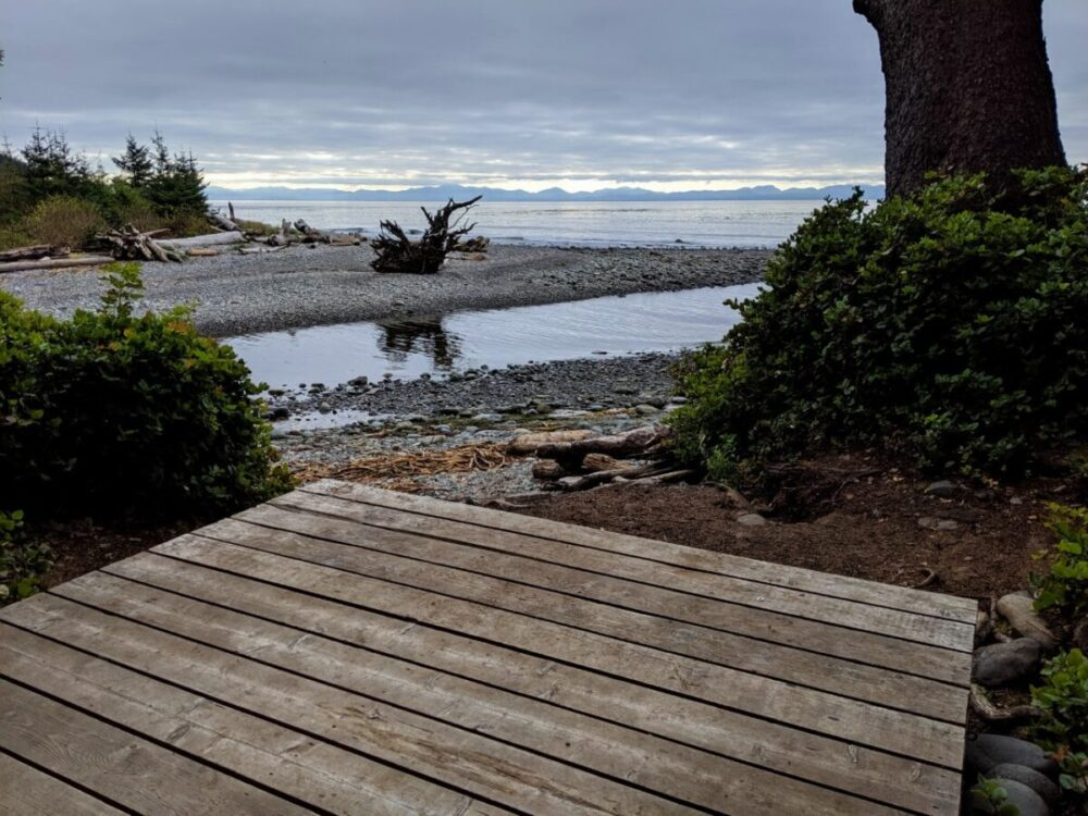 View from wooden tent pad on the Juan de Fuca Trail looking out to the ocean, which is backdropped by mountains