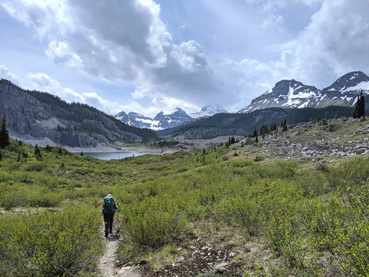 Gemma hiking, approaching Og Lake with mountainous backdrop