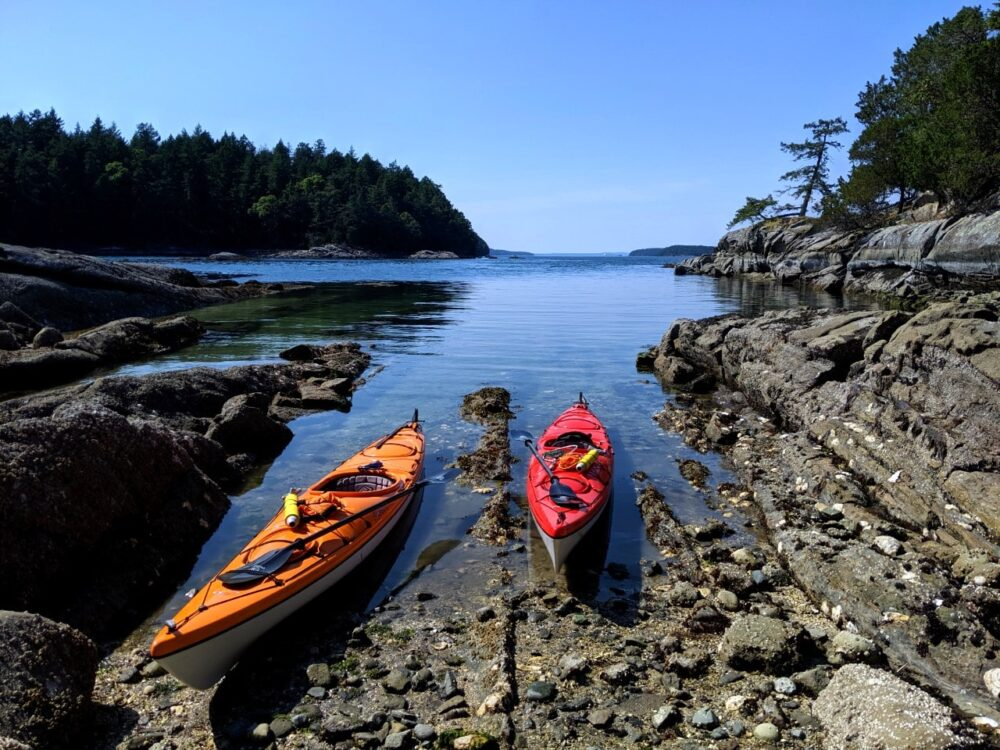 Orange and red kayak partially in water on rocky oyster beach at Chivers Point, Wallace Island