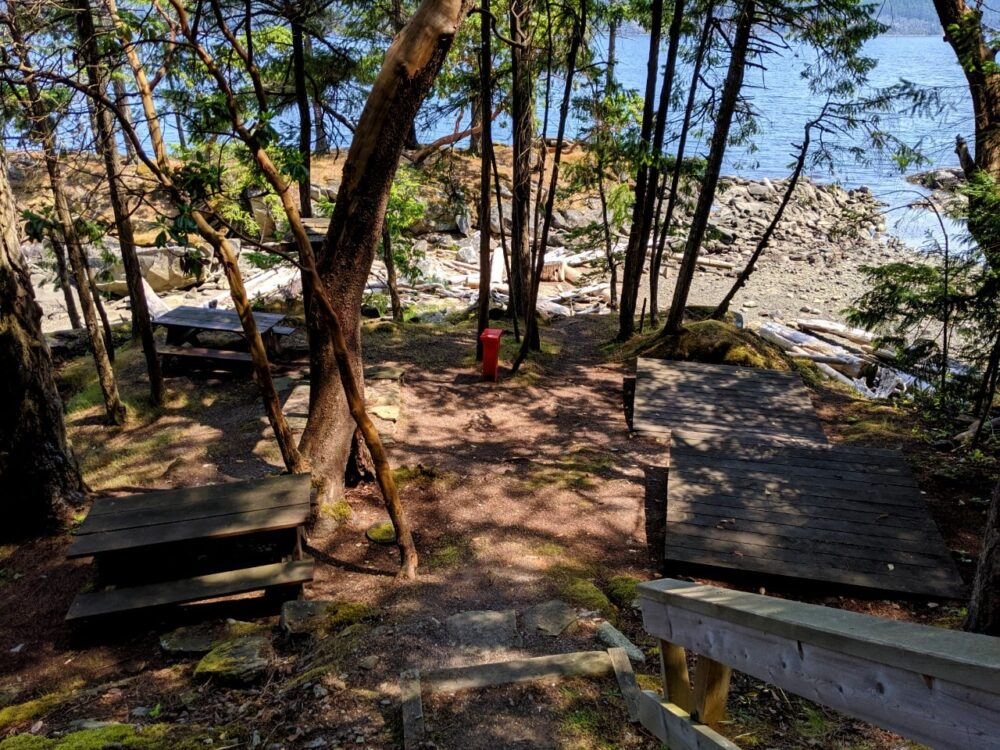 Looking down the stairs at Cabin Bay campground, with two picnic tables and two tent pads