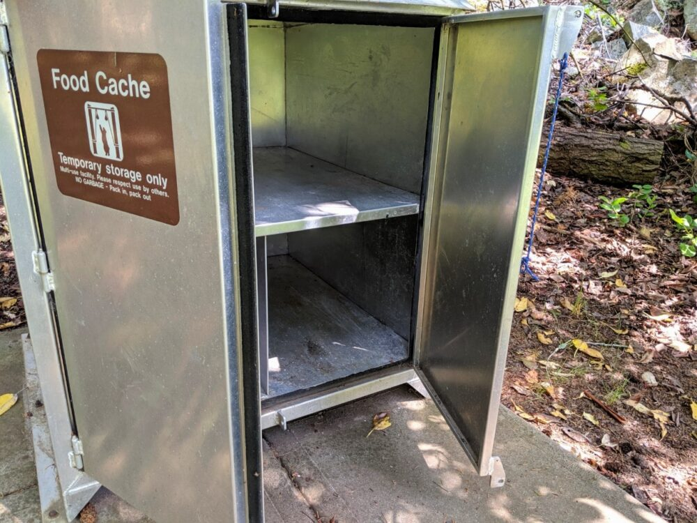A metal food cache with doors wide open at Conover Cove