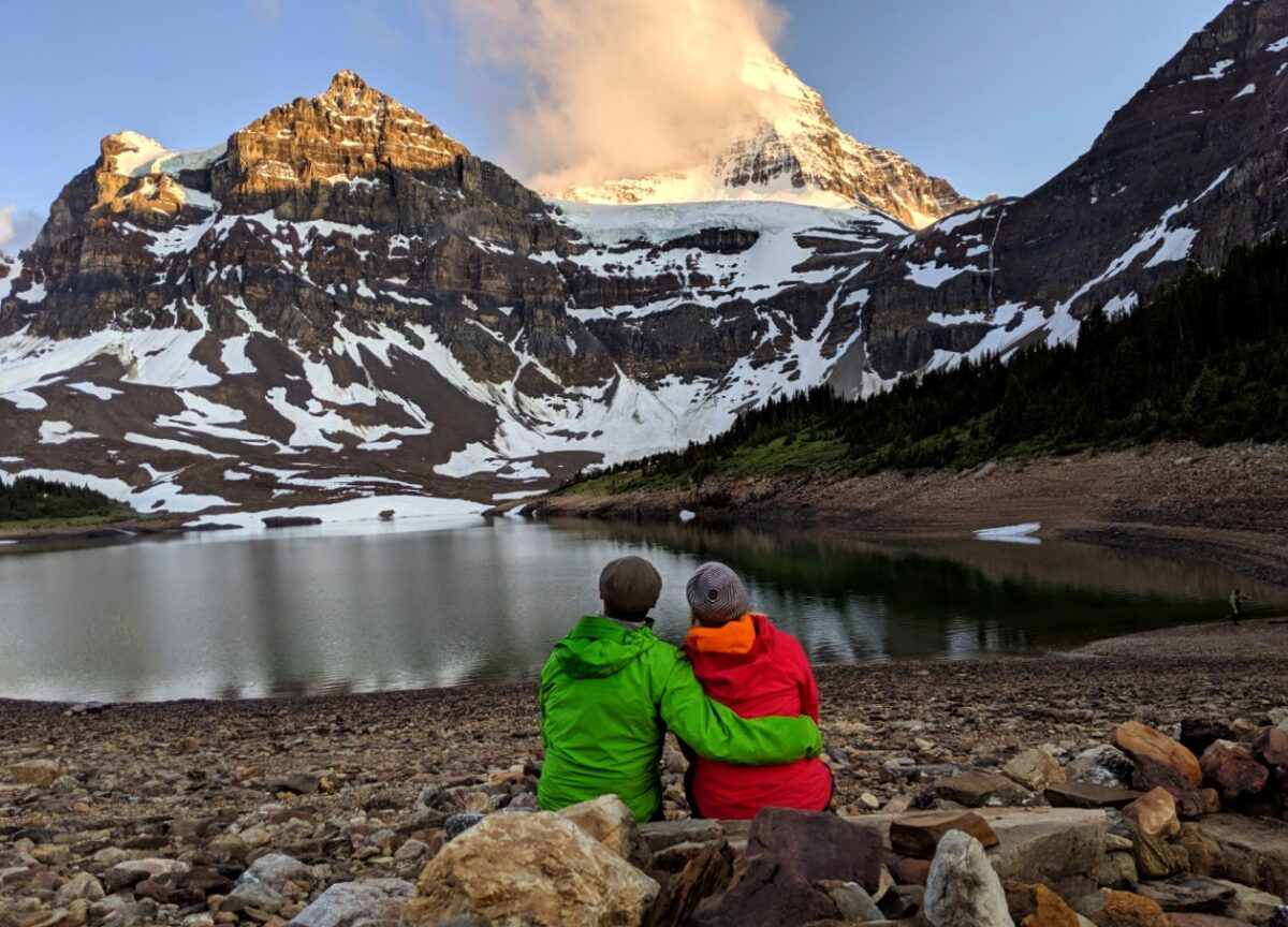 Gemma and JR sit and watch the sunset and Mount Assiniboine (with cloud cover), wearing red and green jackets