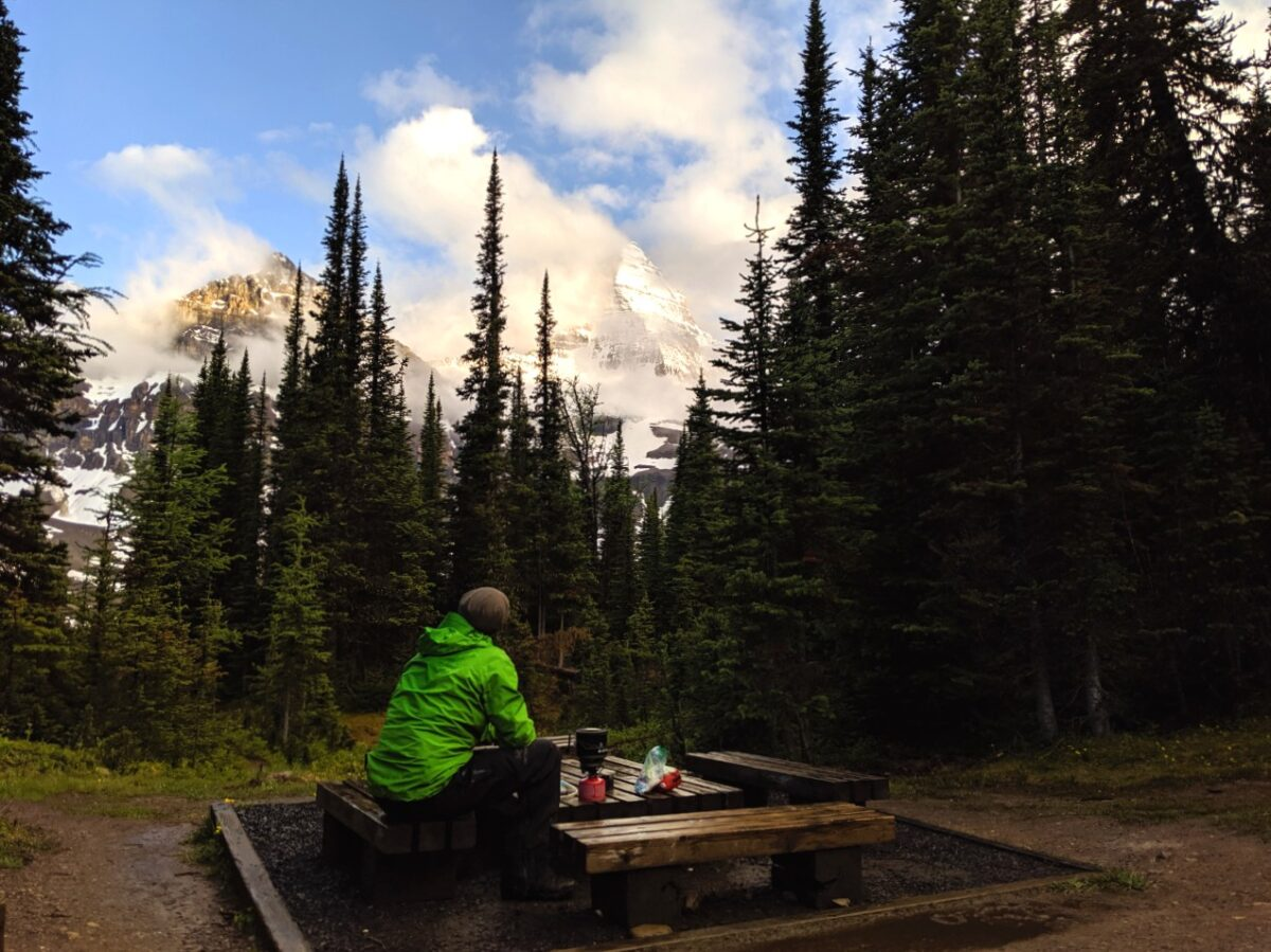 JR sat at cooking area table looking at Mount Assiniboine