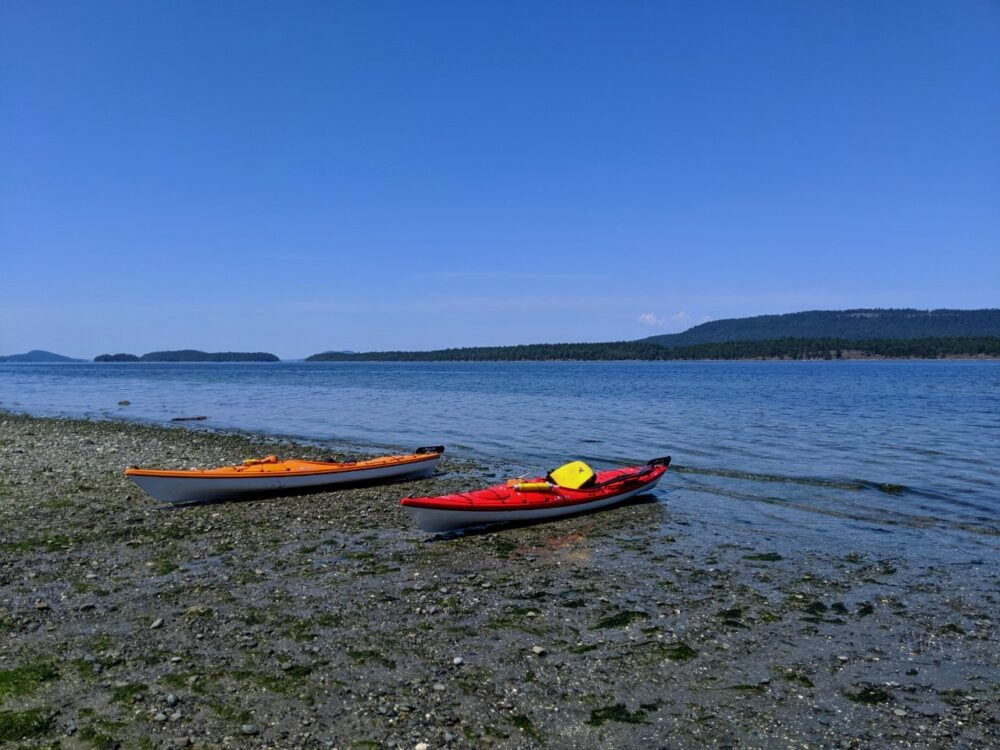 Orange and red kayak on shore at Hudson Point