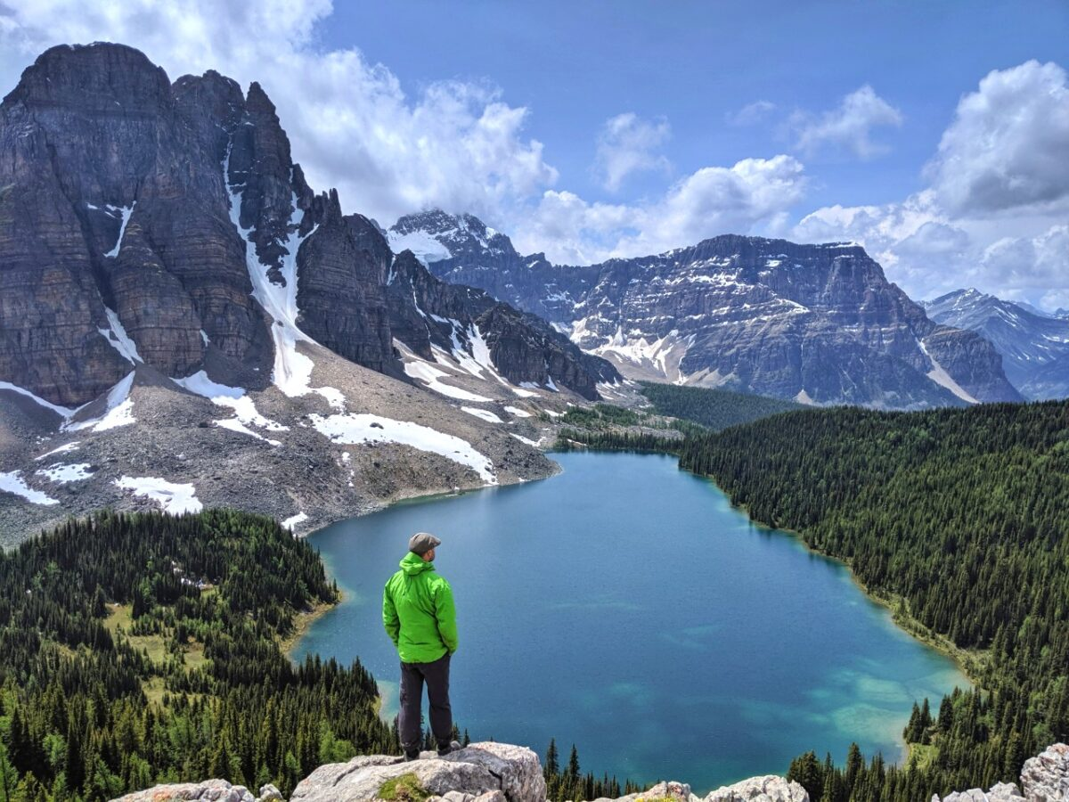 JR standing on a rock looking out at beautiful views of turquoise Cerulean Lake surrounded by mountains in Mount Assiniboine Provincial Park