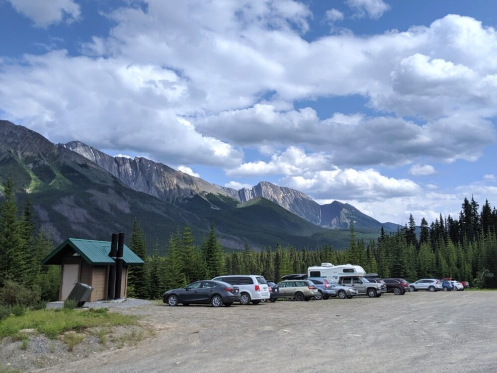 Vehicles parked in parking lot with outhouse and mountain backdrop