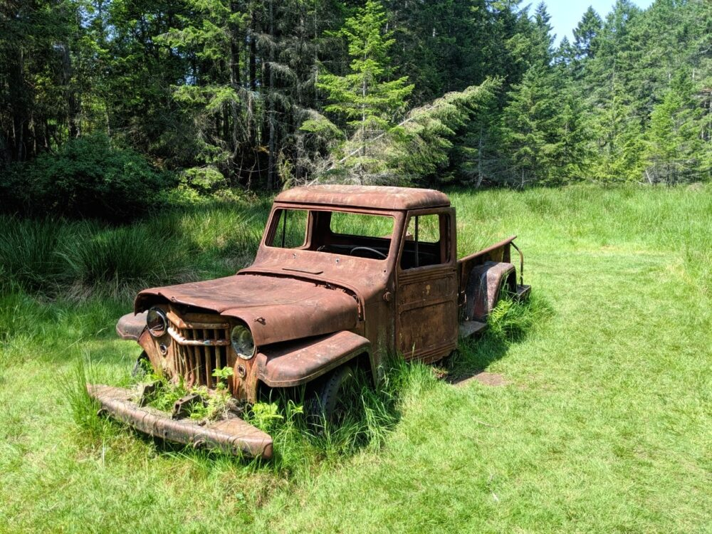 Rusting old truck in a very green meadow near Conover Cove