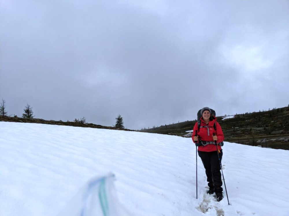 Gemma is standing on snowy hiking trail looking at camera and holding hiking poles. Much of the ground is covered in snow