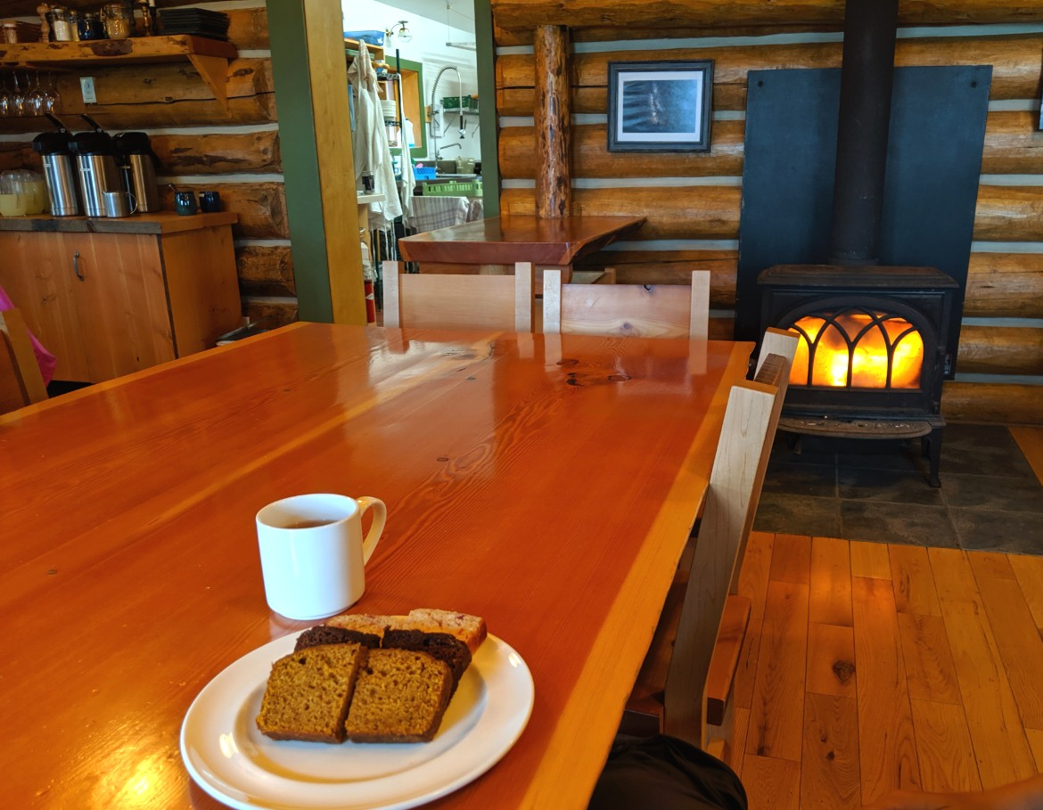 Plate of cake slices and cup of tea in front of the fire at Assiniboine Lodge