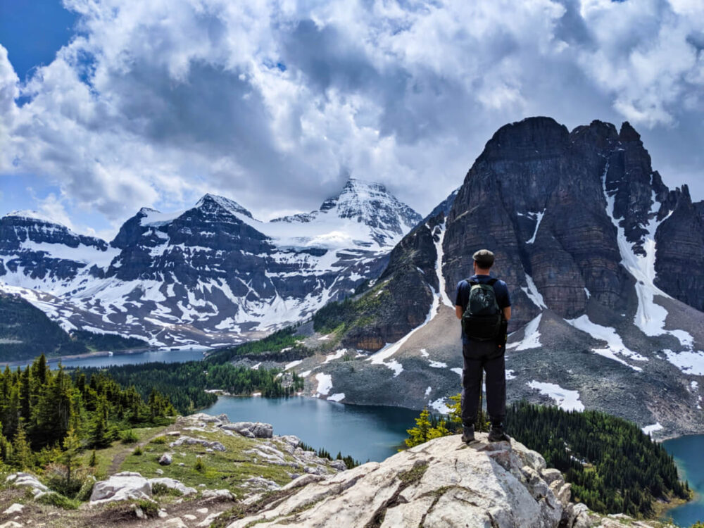 JR stands on a rock in front of impressive elevated view of Mount Assiniboine's pyramidal peak (the top is obscured by cloud), with another peak in front, both of which have bright turquoise coloured lakes at their base