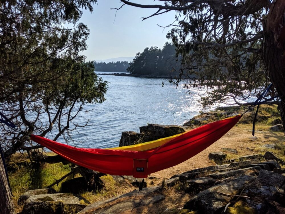 Red and yellow hammock hanging in front of scenic ocean view