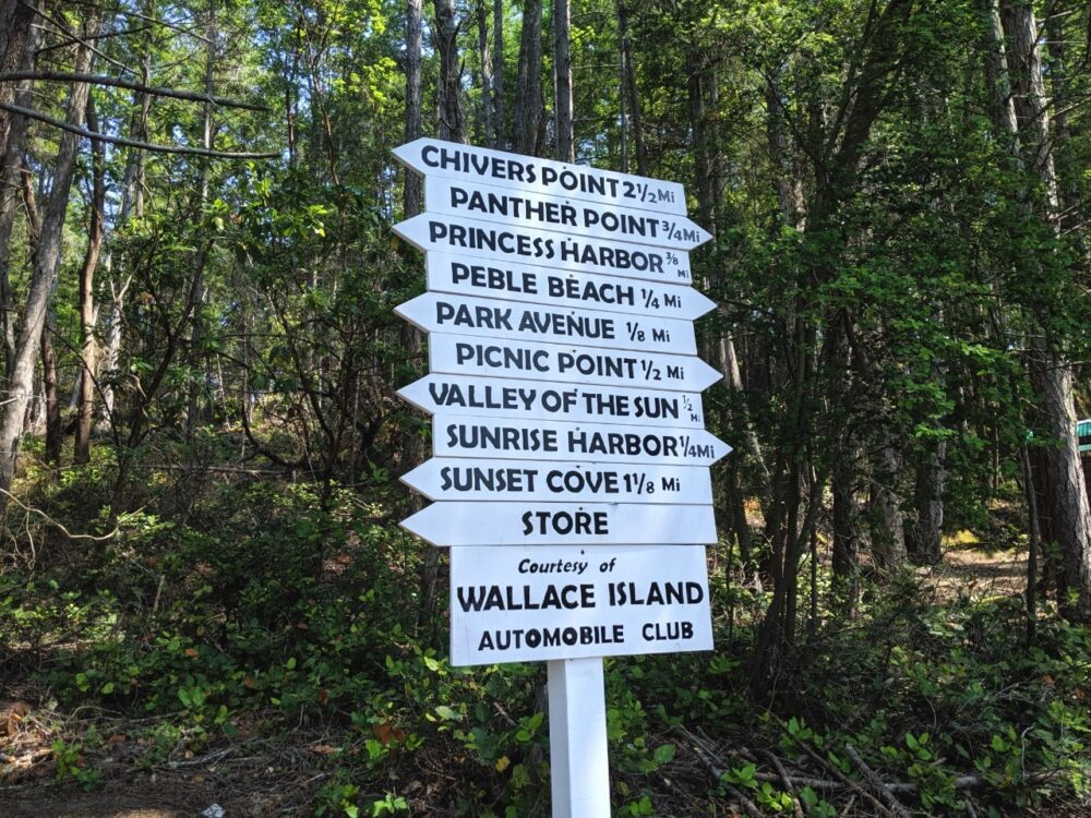 White signs with black text pointing the way to different areas of Wallace Island