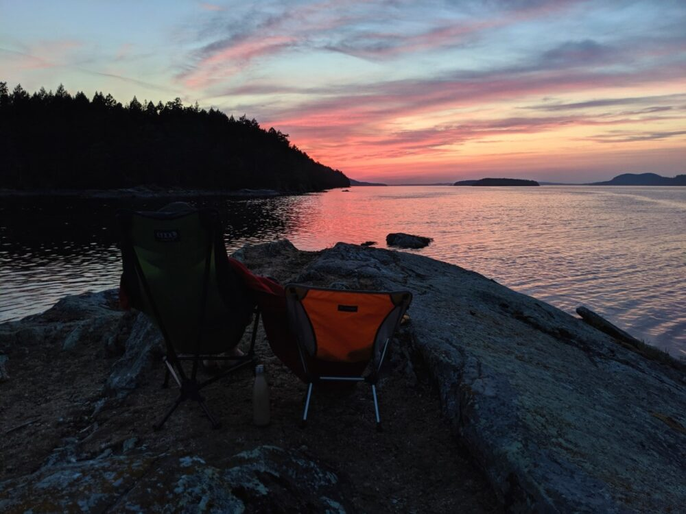 Camp chairs on rock point looking out to pink sunset