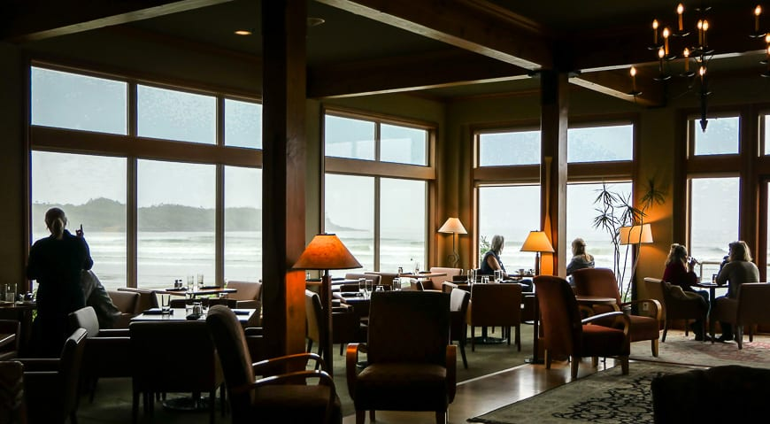 View of dining tables and comfortable chairs in front of large windows looking out to beach