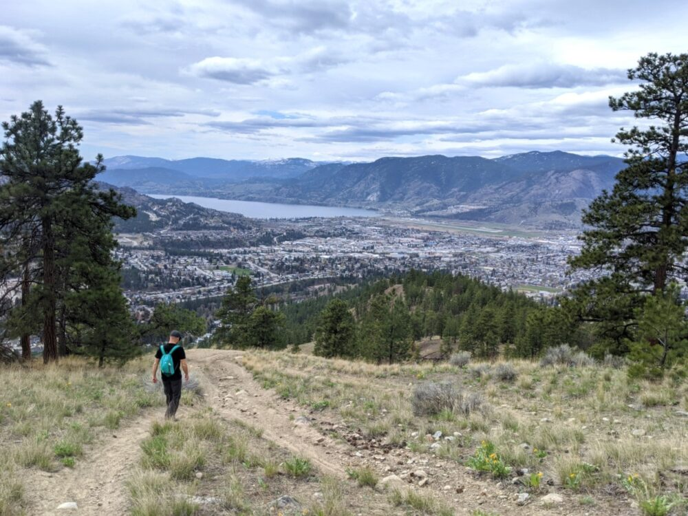 JR hiking down Campbell Mountain with expansive views of Skaha Lake and the city of Penticton behind