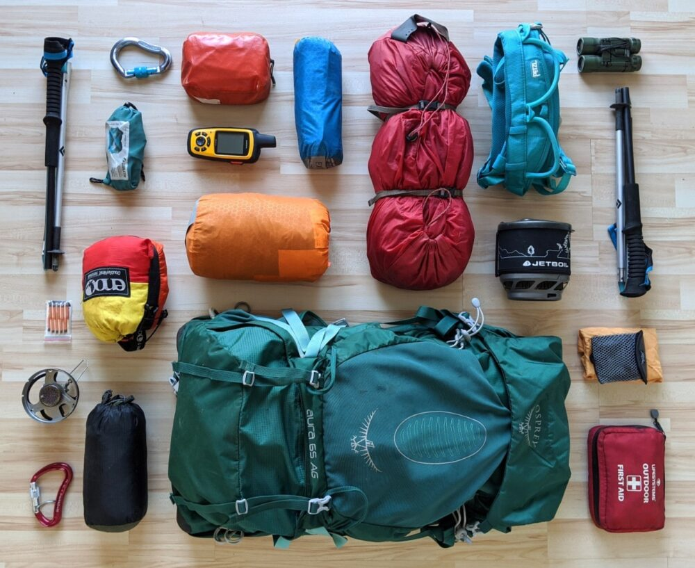Flat lay of various outdoor gear including tent, backpack, hammock, sleeping mat