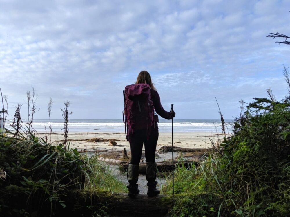 Back view of Gemma standing with backpack and hiking pole in front of sandy beach on the coast of BC