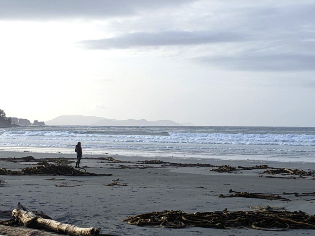 Gemma standing on sandy beach next to Pacific Ocean in Cape Scott Provincial Park