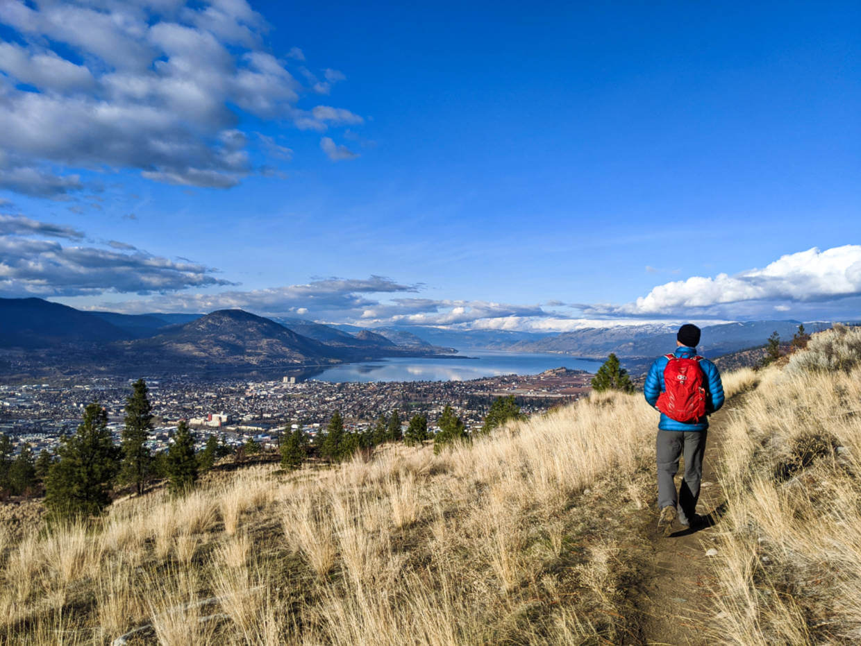 JR hiking along the Gspot Trail on dirt path with elevated views of Okanagan Lake and downtown Penticton ahead