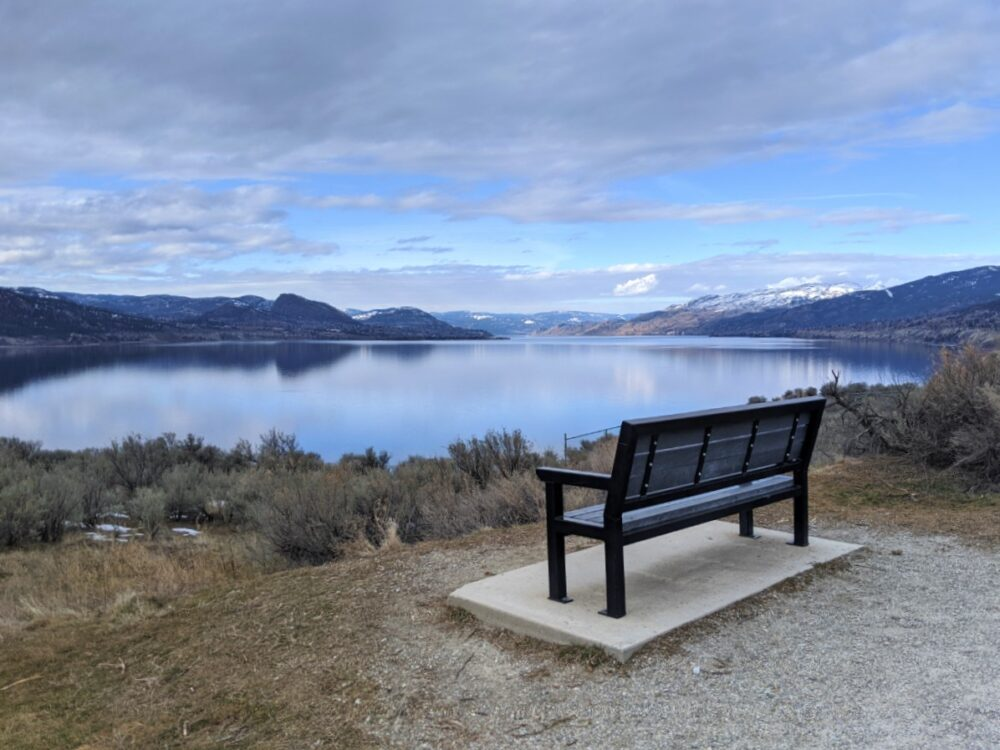 Elevated view of Okanagan Lake from KVR Trail near Penticton with bench in front of cliff