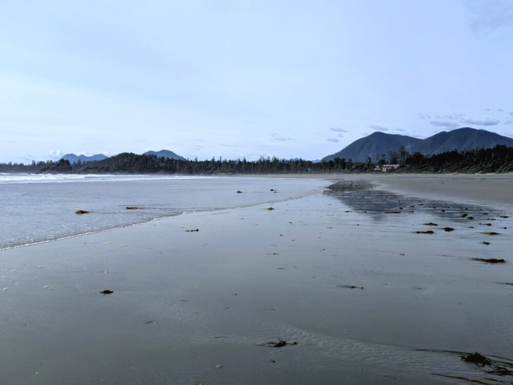 Sandy beach with ocean incoming, backdropped by mountains