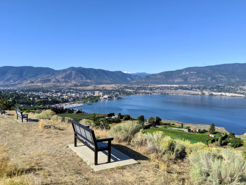 Benches lined up in front of cliff with views towards Penticton with Okanagan Lake and bordering mountains