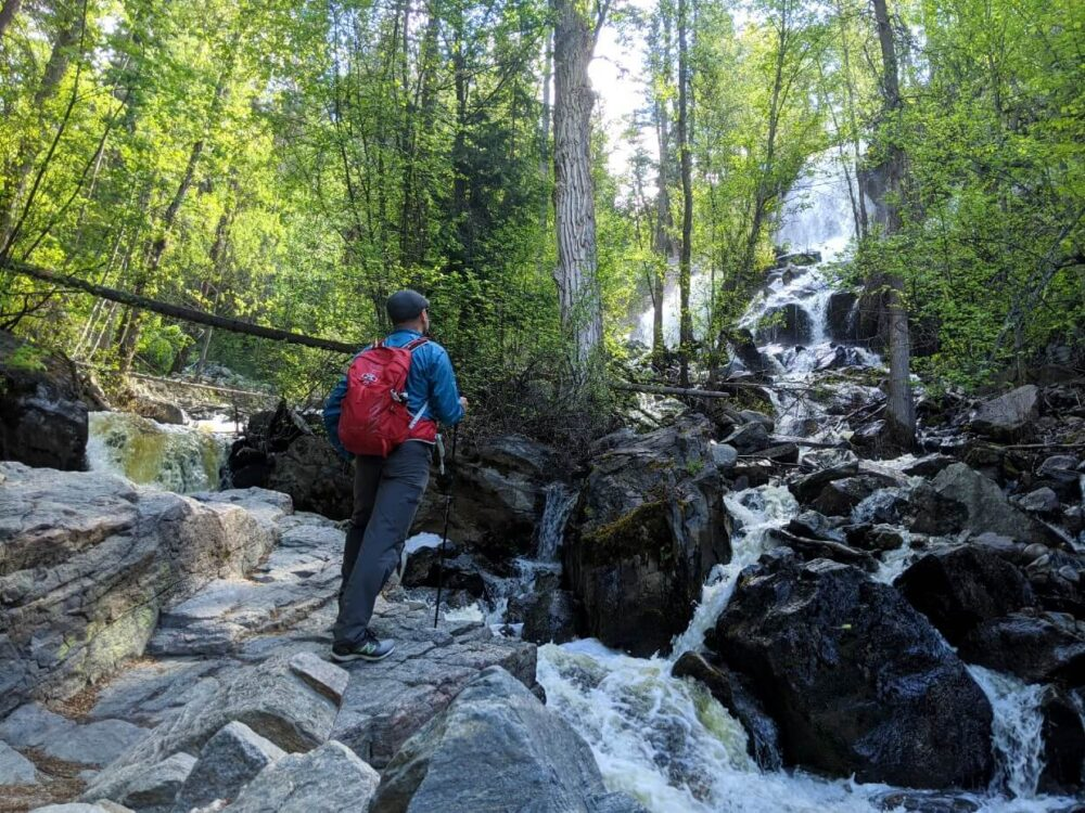 JR is standing on a rock in front of Naramata Creek Falls, a series of cascades in a forest
