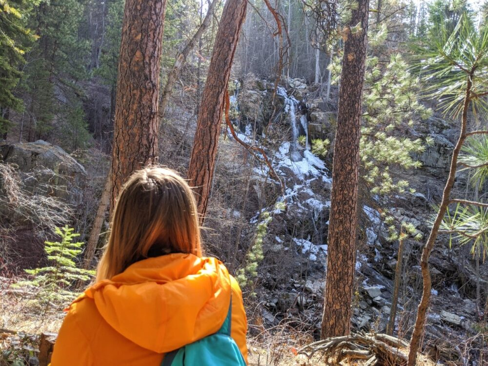 Gemma looking at Naramata Creek Falls through trees