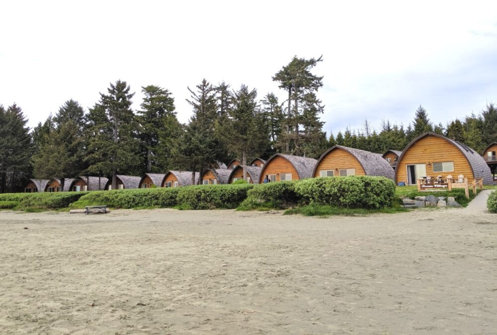 Line of beehive cabins situated behind the sands of Mackenzie beach at Ocean Village in Tofino, one of the best places to stay in Tofino
