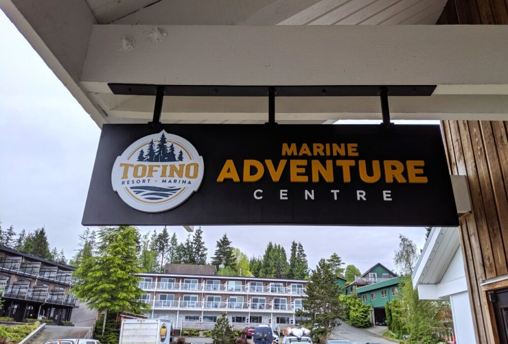 Marine Adventure Centre sign with Tofino Resort + Marina accommodation blocks behind