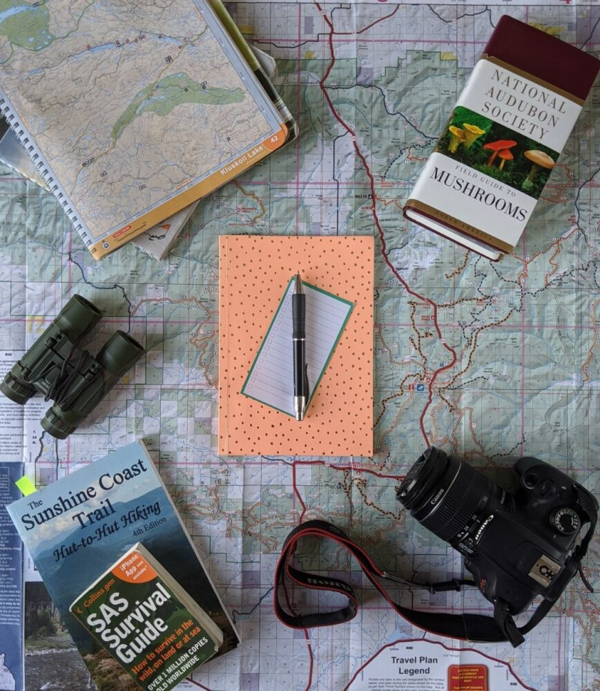 Flat lay of map with books, binoculars, camera, pen and paper