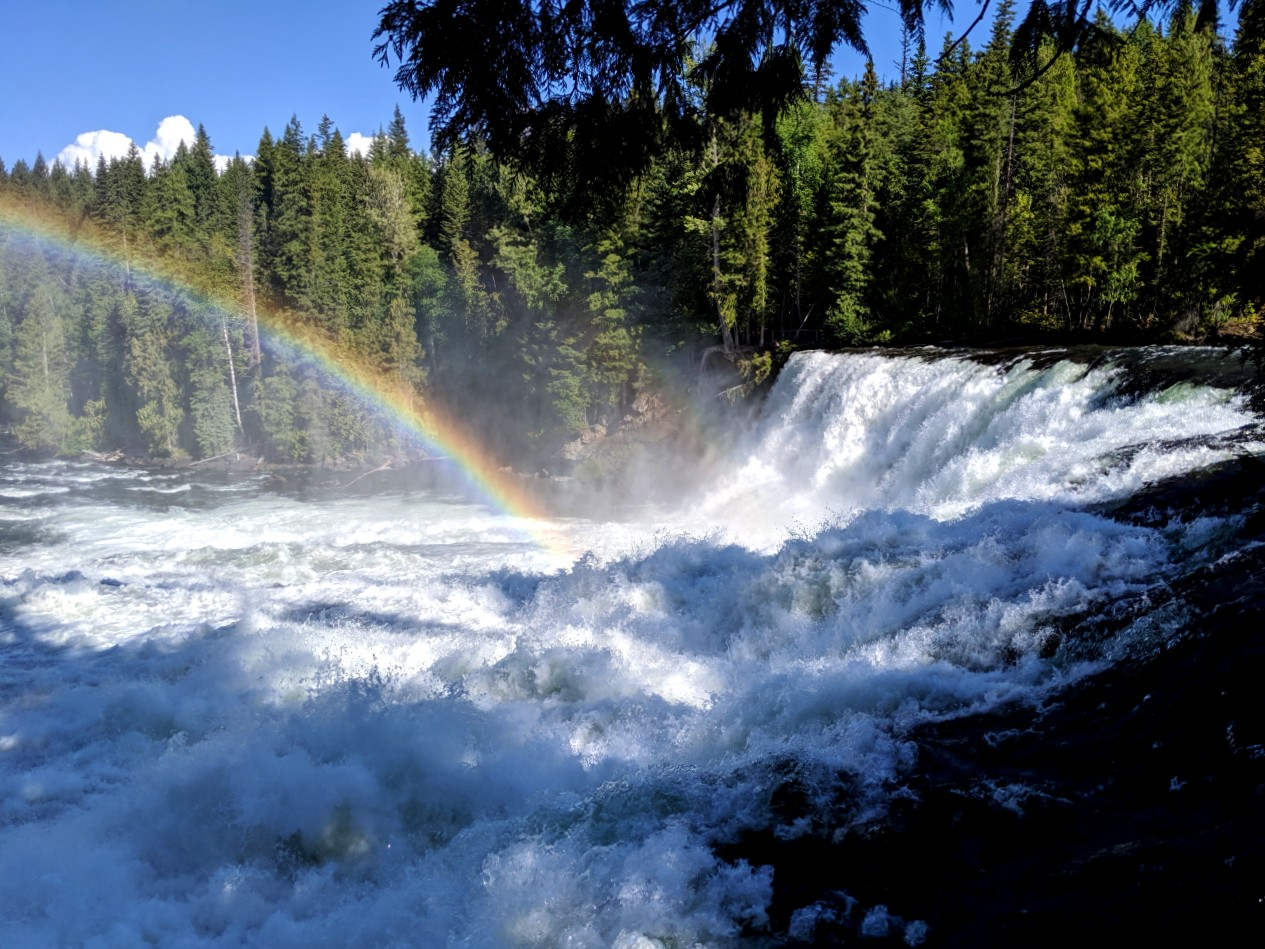 Rainbow leading to rushing waterfall in Wells Gray Provincial Park