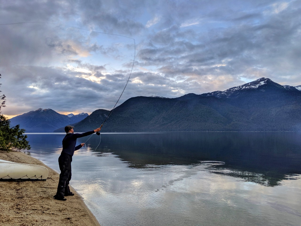 JR fishing with fly fishing pole on the shore of Murtle Lake with mountains behind and calm lake surface