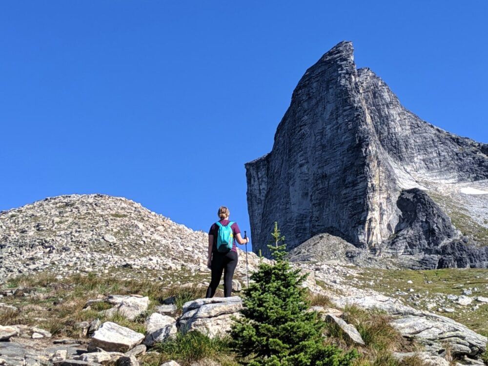 Gemma standing with hiking pole looking up towards the dramatic Gimli Peak in Valhalla Provincial Park