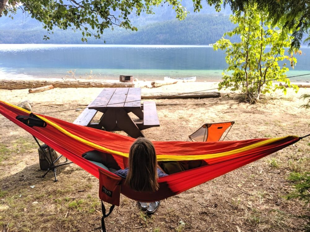 Gemma relaxing in a brightly coloured hammock in front of a picnic table and Slocan Lake, Valhalla Provincial Park