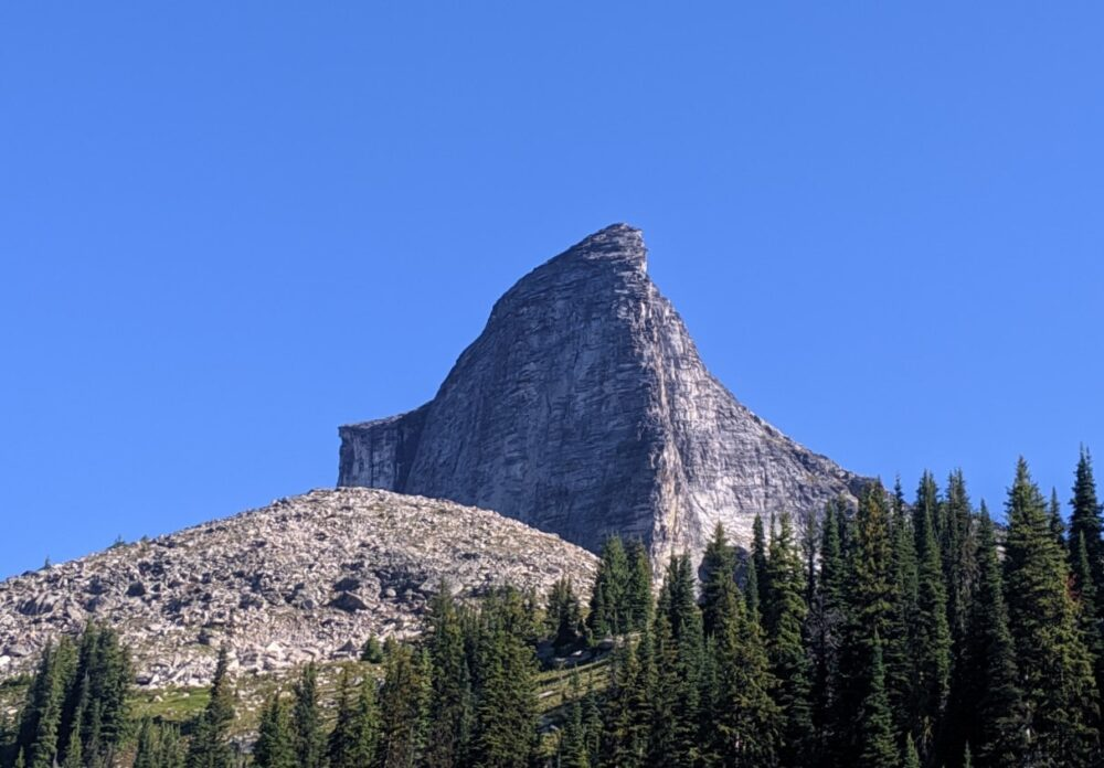 An unusual mountain peak rising out of a rocky ridge and forest in Valhalla Provincial Park