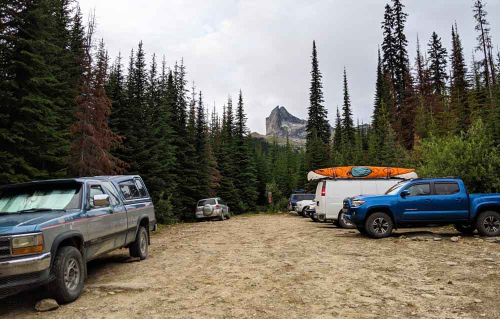 Dirt parking lot with seven vehicles, with the distinctive peak of Gimli in the background