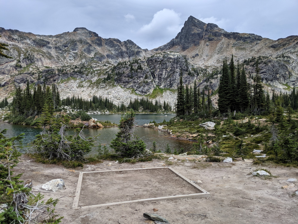 Square ten tad in front of scenic lake view, backdropped by mountains